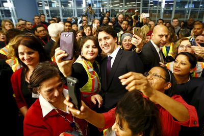 Canada's Prime Minister Justin Trudeau poses with airport staff as they await Syrian refugees to arrive at the Toronto Pearson International Airport in Mississauga, Ontario, December 10, 2015.  After months of promises and weeks of preparation, the first planeload of Syrian refugees was headed to Canada on Thursday, aboard a military plane to be met at Toronto's airport by Trudeau.   REUTERS/Mark Blinch