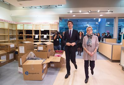 Canadian Prime Minister Justin Trudeau, left, and Ontario Premier Kathleen Wynne tour the facility where winter clothing will be given out to Syrian refugees arriving at Pearson International airport, in Toronto, on Thursday, Dec. 10, 2015. THE CANADIAN PRESS/Nathan Denette