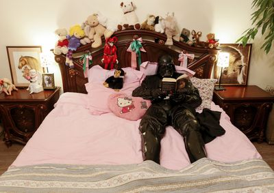 """Darth Mykolaiovych Vader, who is dressed as the """"Star Wars"""" character Darth Vader, poses for a picture as he reads a book in bed at his apartments in Odessa, Ukraine, Dec. 2, 2015. REUTERS/Valentyn Ogirenko"""