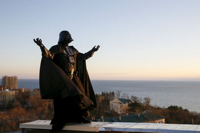 """Darth Mykolaiovych Vader, who is dressed as the """"Star Wars"""" character Darth Vader, poses for a picture as he waits for sunrise on the roof of his apartment block in Odessa, Ukraine, Dec. 4, 2015. REUTERS/Valentyn Ogirenko"""