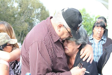 Tina Fontaine's great-aunt and uncle, Thelma and Joseph Favel, watch as Fontaine's body is taken away to be cremated after her funeral at Fort Alexander Church on Sakeeng  First Nation Aug. 23, 2014.