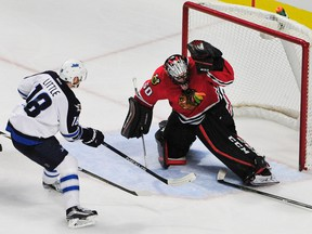 Chicago Blackhawks goalie Corey Crawford (50) makes a save on Winnipeg Jets center Bryan Little (18) during the third period at the United Center. The Blackhawks won 2-0. David Banks-USA TODAY Sports