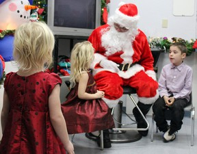 Morgan Vanluven, foreground, isn't so sure about Santa as he speaks to her sister Maci and brother Xavier at the Community Christmas dinner hosted by The Salvation Army Rideau Heights Corps in Kingston, Ont. on Saturday December 12, 2015. Steph Crosier/Kingston Whig-Standard/Postmedia Network