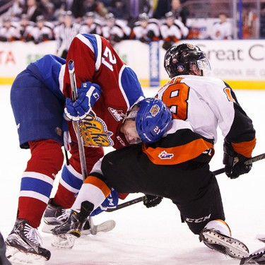 Edmonton's Tyler Robertson (21) and Medicine Hat's Mason Shaw (18) tie up during a faceoff at a WHL game between the Edmonton Oil Kings and the Medicine Hat Tigers at Rexall Place in Edmonton, Alta. on Sunday December 13, 2015. Ian Kucerak/Edmonton Sun/Postmedia Network