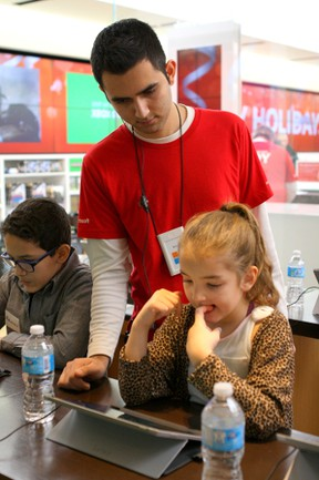 Amir Khiabani helps Bashira James, 7, learn to code during the Hour of Code event at  the Microsoft store in West Edmonton Mall on Sunday, Dec. 13, 2015. (CLAIRE THEOBALD/ Edmonton Sun)