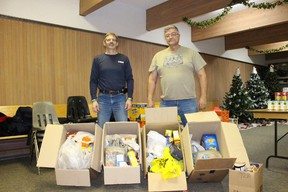 Greg Young, right, of the Vermilion Ridge Riders, presents food collected at the Snowmobile Expo to Derek Collins of the Vermilion Food Bank.