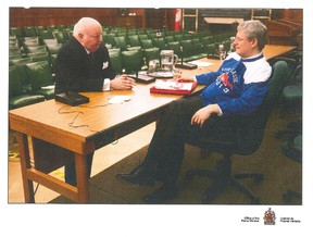 Senator Mike Duffy and former prime minister Stephen Harper are shown at a February 2012 caucus meeting in a handout photo that was entered as evidence at the Duffy trail on Tuesday, Dec. 15, 2015. THE CANADIAN PRESS/HO