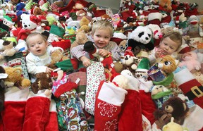 Liam Down-Elliott, eight months old, left, Noah Down-Elliott, 3, and Isabella Evans-Sweet, 10 months old, sit in the middle of more than 225 Christmas stockings at the Kingston Community Health Centres in Kingston on Tuesday. The stockings were donated to children in the centres' programs. (Michael Lea/The Whig-Standard)