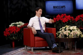 Canada's Prime Minister Justin Trudeau jokingly checks his watch during a Maclean's magazine town hall in Ottawa, Canada, December 16, 2015. REUTERS/Chris Wattie