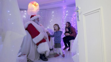 Five-year-old Leila Matheson reacts as she meets actor John Field, dressed as Santa Claus, at a Christmas grotto at a dental practice in north London, Britain, Dec. 12, 2015.  REUTERS/Stefan Wermuth