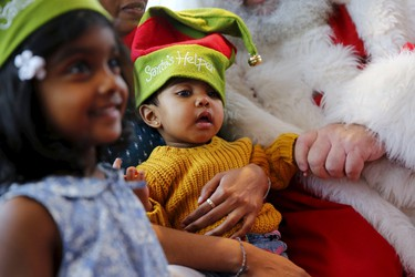 Four-year-old Aarshika Kokulam (L) and her one-year-old brother Prithika pose for a photograph with actor John Field, dressed as Santa Claus, during a City Cruises boat tour on the River Thames in London, Britain, Nov. 28, 2015. REUTERS/Stefan Wermuth