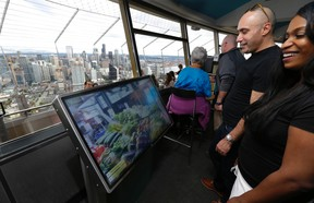 In this Sept. 19, 2014, file photo, Anan Bishara, left, and Denise Burrell, right, both from New York, check out a virtual reality display that lets visitors explore the Pike Place Market and other attractions atop the Space Needle in Seattle. The high-tech attractions are part of an explosion of virtual reality in the travel industry. (AP Photo/Ted S. Warren, File)