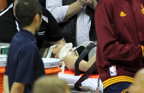 Ellie Day, wife of PGA Tour golf player Jason Day, is carried off the floor in a stretcher after Cleveland Cavaliers' LeBron James collided with her out of bounds in a game against the Oklahoma City Thunder in Cleveland on Dec. 17, 2015. (John Kuntz/The Plain Dealer via AP)