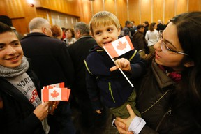 Zawenawedian Dawdian, 2, is held by his mother Mario and was one of a group of sponsored Syrian refugees who arrived in Toronto on Dec. 16, 2015. (Michael Peake/Toronto Sun)