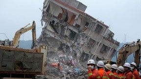 Rescuers search for potential survivors near damaged buildings following a landslide at an industrial park in Shenzhen, in south China's Guangdong province, Tuesday, Dec. 22, 2015. (AP Photo/Andy Wong)