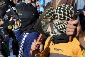 A masked Palestinian boy holds a chopper during a rally organized by Islamic Jihad in Rafah in the southern Gaza Strip December 18, 2015. REUTERS/Ibraheem Abu Mustafat