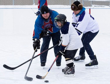Members of the Edmonton Police Service and neighbourhood children take part in the 7th Annual McCauley Cup hockey game at the McCauley Community Rink, 10752 - 96 St., in Edmonton Alta. on Wednesday Dec. 23, 2015. David Bloom/Edmonton Sun/Postmedia Network