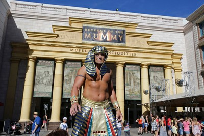 In this Thursday, Oct. 22, 2015 photo, a character actor greets visitors at the entrance to the Revenge of the Mummy ride at Universal Studios in Orlando, Fla. In the last 25 years, Universal Orlando has emerged from the shadow of its older sister park to forge its own identity celebrating the entertainment industry.   (AP Photo/John Raoux)