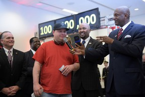 Passenger Larry Kendrick, middle, speaks next to Hartsfield-Jackson Atlanta International Airport Manager Miguel Southwell, right, during a ceremony naming Kendrick the airport's 100 millionth passenger on Sunday, Dec. 27, 2015, in Atlanta. The airport that calls itself the world's busiest announced on its social media sites said it served its 100 millionth passenger this year. (Kent D. Johnson/Atlanta Journal-Constitution via AP)
