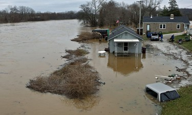 People move some of their belongings to higher ground on Tuesday, Dec. 29, 2015, as the Meramec River continues to rise next to the Gravois Road bridge in old town Fenton, Mo. Torrential rains over the past several days pushed already swollen rivers and streams to virtually unheard-of heights in parts of Missouri and Illinois. Record flooding was projected at some Mississippi River towns, and the Meramec River near St. Louis was expected to get to more than 3 feet above the previous record by late this week  (J.B. Forbes /St. Louis Post-Dispatch via AP)