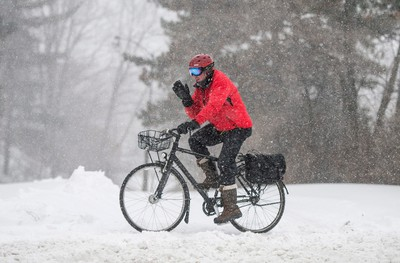 A cyclist finds a clear path to ride during the first winter storm of the year in Ottawa on Tuesday, Dec. 29, 2015. Environment Canada forecasted up to 20 centimetres of snow for the Ottawa region. THE CANADIAN PRESS/Justin Tang