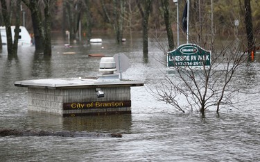 In this Monday, Dec. 28, 2015 photo, a trailer park in Branson, Mo., is flooded by the waters of Lake Taneycomo. (Nathan Papes/The Springfield News-Leader via AP)