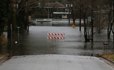 In this Monday, Dec. 28, 2015 photo, a street is closed by flood water in Branson, Mo.(Nathan Papes/The Springfield News-Leader via AP)