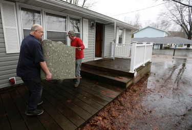 In this Monday, Dec. 28, 2015 photo, Jack Harris, left, and Brinton Bushong carry a chair to a truck as flood waters approach Harris's house in Branson, Mo.(Nathan Papes/The Springfield News-Leader via AP)