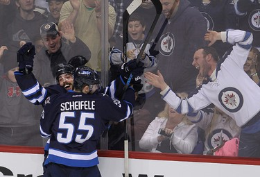 Fans react as Winnipeg Jets centre Mathieu Perrault (l) celebrates his fourth goal against the Florida Panthers with teammate Mark Scheifele during NHL hockey in Winnipeg, Man. Tuesday, January 13, 2015. Brian Donogh/Winnipeg Sun/QMI Agency