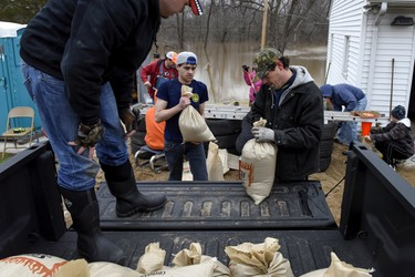 Volunteers prepare to transport sandbags which will be used to protect homes from flooding, following several days of heavy rain in Arnold, Missouri, December 30, 2015. REUTERS/Kate Munsch