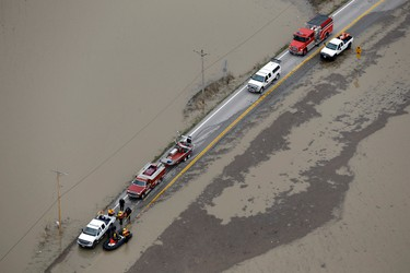 In this aerial photo, rescue personnel wait on a flooded road Wednesday, Dec. 30, 2015, in West Alton, Mo. A rare winter flood threatened nearly two dozen federal levees in Missouri and Illinois on Wednesday as rivers rose, prompting evacuations in several places. (AP Photo/Jeff Roberson)