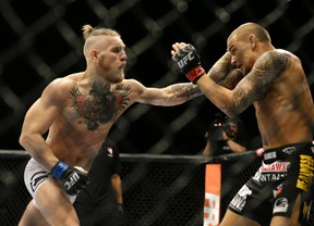Conor McGregor, left, and Dustin Poirier, exchange hits during their fight in Las Vegas in 2014.  (AP Photo/John Locher,File)