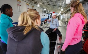 Olympic women's bobsled champion Kaillie Humphries, second from right, gives instruction to her crew while training in Calgary on Saturday, Jan. 2, 2016. Humphries will get to pilot four-man sleds on her return to the World Cup circuit, but her crew will be female and not male. THE CANADIAN PRESS/Jeff McIntosh