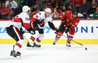Jan 3, 2016; Chicago, IL, USA; Chicago Blackhawks right wing Marian Hossa (81) passes the puck away from Ottawa Senators left wing Mike Hoffman (68) and defenseman Patrick Wiercioch (46) during the first period at the United Center. Mandatory Credit: Jerry Lai-USA TODAY Sports