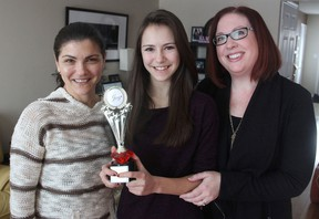 Young actor Alexandra Hook, centre, flanked by her mother Viktoria Koganova, left, and talent agency owner Tammy Godefroy, holds a Joey Award at her home in Kingston on Friday, a national award for her work in television commercials. (Michael Lea/The Whig-Standard)