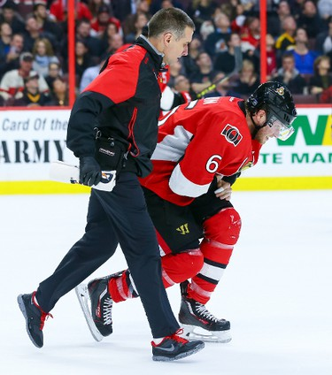 Ottawa Senators right wing Bobby Ryan (6) is helped off the ice by trainer Gerry Townend during NHL action against the Boston Bruins in Ottawa, Ont. on Saturday January 9, 2016. Errol McGihon/Ottawa Sun/Postmedia Network
