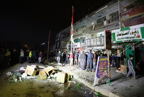 People gather in front of the mall in Baghdad, Iraq, Monday, Jan. 11, 2016. Gunmen stormed into a Baghdad mall on Monday after setting off a car bomb and launching a suicide attack at its entrance, killing at least a dozen people in the city's mainly Shiite east, Iraqi officials said. (AP Photo)