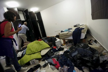 """Reuters journalists inspect the bedroom of a safe house, where five people were shot dead during an operation on Friday to recapture the drug lord Joaquin """"El Chapo"""" Guzman, at Jiquilpan Boulevard in Los Mochis, in Sinaloa state, Mexico, Jan. 11, 2016. (REUTERS/Edgard Garrido)"""