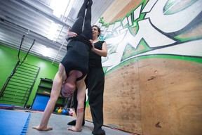 Andralyn Zayn teaches Marissa Gough how to properly do a handstand during a training session at Deflying Fitness, in Vancouver, Sunday, Jan. 10, 2016. (THE CANADIAN PRESS/Jonathan Hayward)