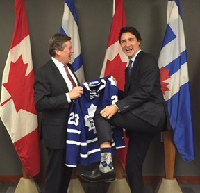 Prime Minister Justin Trudeau shows off his Montreal Canadiens socks as Toronto Mayor John Tory presents him with a Maple Leafs jersey Wednesday, Jan. 13, 2016 at City Hall. (Twitter photo)