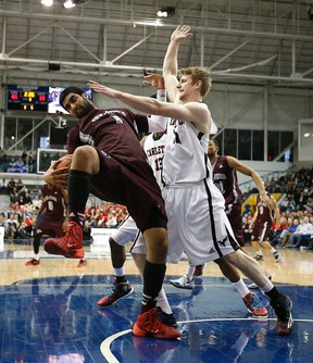 Carleton's Connor Wood leans on Ottawa's Vikas Gill as Carlton defeated Ottawa 93-46 to win the CIS university national basketball championship in Toronto, Ont. on Sunday March 15, 2015. Michael Peake/Toronto Sun/QMI Agency
