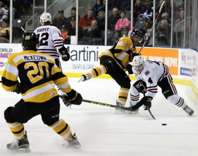 Niagara Ice Dog's Vince Dunn handles the puck past Kingston Frontenac's Spencer Watson to face Roland McKeown during Ontario Hockey League action at the Rogers K-Rock Centre in Kingston, Ont. on Saturday January 16, 2016. Steph Crosier/Kingston Whig-Standard/Postmedia Network