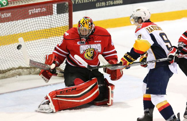 Owen Sound goalie Michael McNiven (left) turns away a shot by the Erie Otters' Kyle Maksimovich in the Attack's 8-0 win last season in Ontario Hockey League play. McNiven was invited to Hockey Canada's national junior team selection camp on Tuesday.