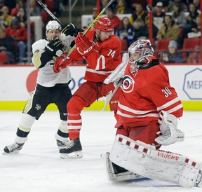 Carolina Hurricanes goalie Cam Ward (30) deflects a shot as Hurricanes' Jaccob Slavin and Pittsburgh Penguins' Patric Hornqvist, of Sweden, struggle at rear during the first period of an NHL hockey game in Raleigh, N.C., Tuesday, Jan. 12, 2016. Carolina won 3-2 in overtime. (AP Photo/Gerry Broome)