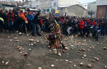 Revellers throw turnips at the kneeling Jarramplas as he makes his way through the streets beating his drum during the Jarramplas traditional festival in Piornal, southwestern Spain, January 20, 2015. Even though the exact origins of the festival are not known, various theories exist including the mythological punishment of Caco by Hercules, a relation to ceremonies celebrated by the American Indians that were seen by the first conquerors, to a cattle thief ridiculed and expelled by his village neighbours. REUTERS/Sergio Perez (SPAIN - Tags: SOCIETY)