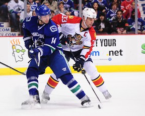 Florida Panthers defenceman Willie Mitchell (33) defends against Vancouver Canucks forward Alexandre Burrows (14) at Rogers Arena. (Anne-Marie Sorvin/USA TODAY Sports)