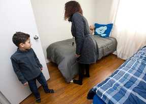 Syrian national Mohammad Ghozlan, 7, watches as Cross Cultural Learner Centre housing coordinator Jerusalem Berhane looks at the furniture in the bedroom he shares with one of his siblings in London, Ont. on Tuesday January 19, 2016. (CRAIG GLOVER, The London Free Press)