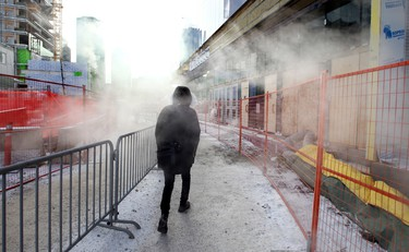 Pedestrians in the mist. A man walks past some steam near the new Rogers Place in Edmonton, Alta., on Jan.16, 2015. Perry Mah