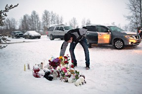 A resident of La Loche, Sask., pays his respects on Saturday January 23, 2016 to the victims of a Friday school shooting. The shooting left four people dead. (THE CANADIAN PRESS/Jason Franson)