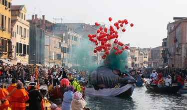 Boats sail along Rio Cannnaregio during the water parade, part of the Venice Carnival, in Venice, Italy, Sunday, Jan. 24, 2016. The Venice carnival in the historical lagoon city attracts people from around the world. (AP Photo/Luca Bruno)
